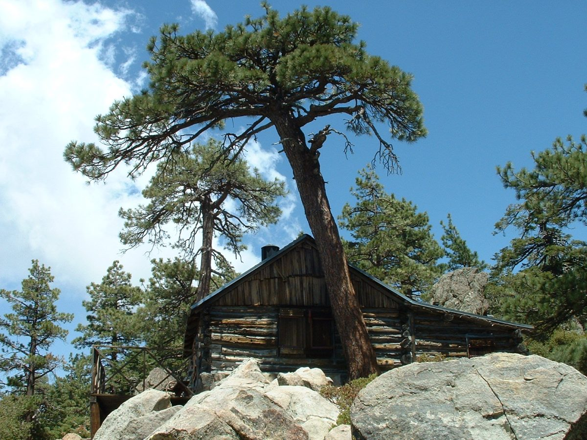 photo of a rustic log cabin in the mountains